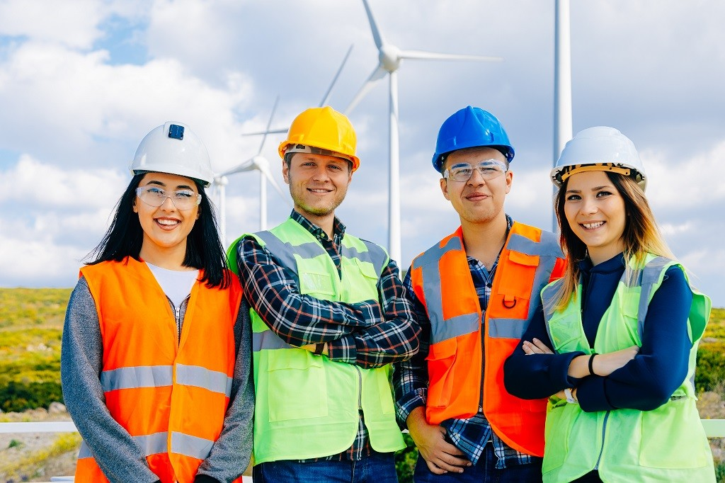 Group portrait of power generation station workers in a windmill farm