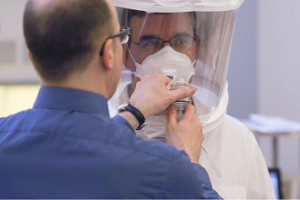 Man performing respirator fit testing on a worker