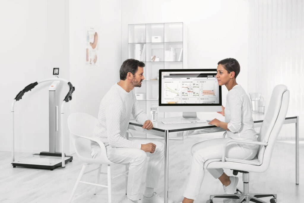 two people looking at medical charts on computer
